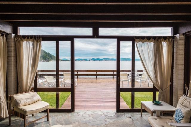 Veľké sklenené dvere otvorené smerom na záhradu, kde je mólo a jazero.jpg