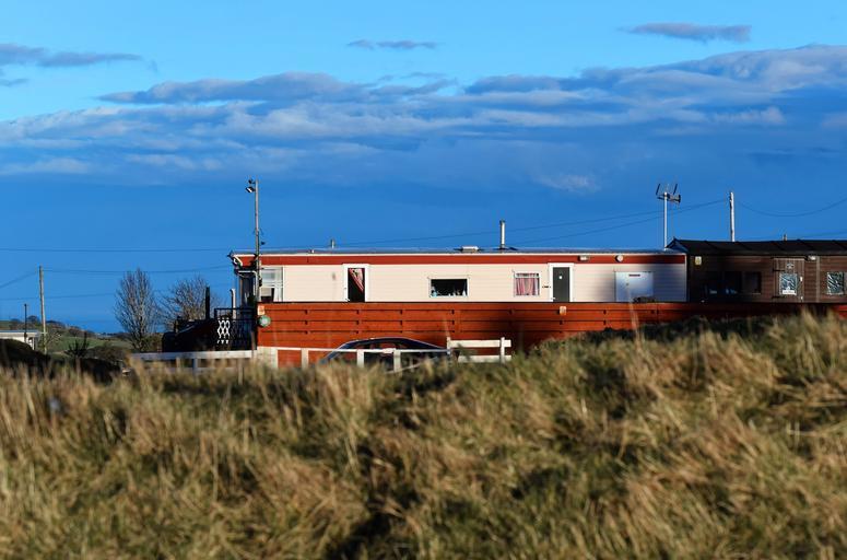 Hnedo-biely mobilný dom postavený na lúke vo vysokej suchej tráve