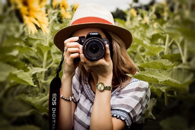 Žena v klobúku stojí medzi slnečnicami a fotografuje.jpg