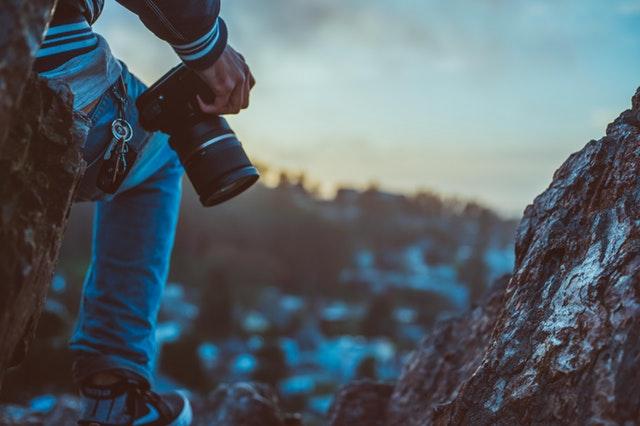 Muž s fotoaparátom v ruke lezie po zasnežených skalách.jpg