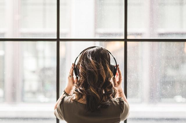 žena sú slúchadlami na ušiach stojí pred veľkým oknom