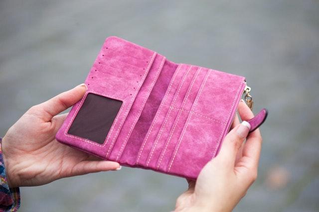 Žena drží v rukách koženú ružovú peňaženku